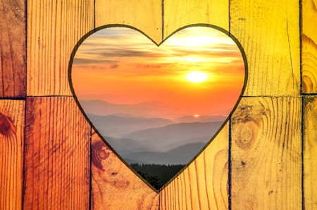 Mountain landscape at sunset in a wooden frame. Wooden frame with a heart in the middle and mountain landscape.