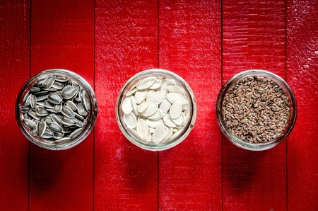 roughage: Sunflower, pumpkin and linseed seeds. Healthy food in glass jars on a red wooden table. Stock Photo