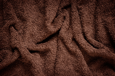 furry: Furry wrinkled blanket texture. Close-up of brown material, may be used as background.