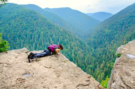 A tourist on the precipice with mountains in the background. Young woman on the precipice in Slovak Paradise National Park. Stock Photo