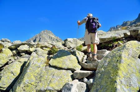 HIGH TATRA, SLOVAKIA - AUGUST 20, 2015: Hiker in mountains. The old man hiking to the top in High Tatra, Slovakia.