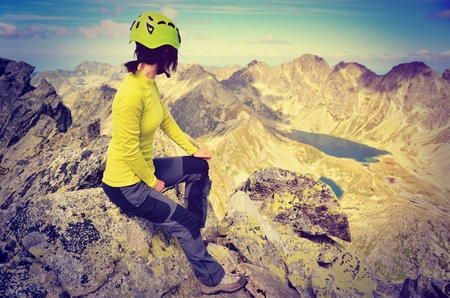 admiring: Tourist admiring the beautiful mountain valley in vintage style.. Young woman on a mountain top in High Tatra, Slovakia. Stock Photo