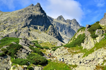 HIGH TATRA, SLOVAKIA - AUGUST 19, 2015: Tourists in a beautiful mountain valley. Tourists climbing the mountain peaks in the High Tatra, Slovakia.