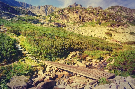 Summer mountain landscape in vintage style. Wooden bridge in the valley and rocky peaks in High Tatra, Slovakia.