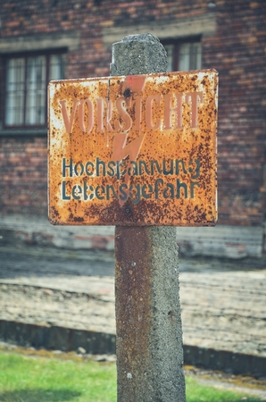 tragedies: OSWIECIM, POLAND - MAY 12, 2016: Sign warning of the danger of the fence in concentration camp Auschwitz-Birkenau in Oswiecim, Poland.