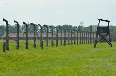 concentration camp: OSWIECIM, POLAND - MAY 12, 2016: Block of concentration camp Auschwitz Birkenau II behind the fence of barbed wire in Brzezinka, Poland.