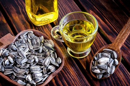 roughage: Sunflower oil and sunflower seeds on a wooden table.