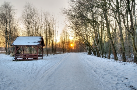 Winter sunset landscape. The road in the forest on the background of sunset.