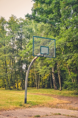 Basketball basket among the green trees. Basketball court in a city park. Stock Photo