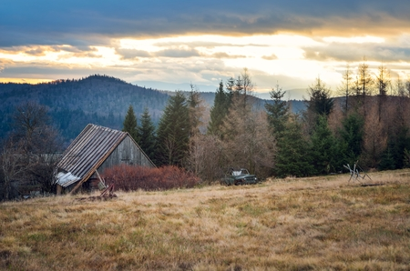 Beautiful mountain autumn landscape. Wooden cabin on a clearing in the mountains.