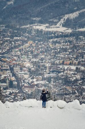ZAKOPANE, POLAND - DECEMBER 30, 2018: Tourist taking pictures of the city from the Gubalowka peak in Zakopane, Poland. 新聞圖片
