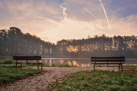 Morning autumn landscape. Wooden benches by the pond of the city park.