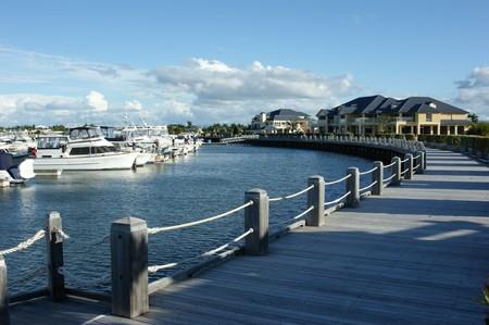 literas: Un largo de madera boardwalk alrededor de una compleja de marina de barco  Foto de archivo