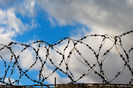 Barbed wire on the background of blue-grey sky photo