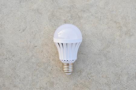 led bulb: LED Bulb on the white concrete Stock Photo