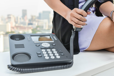 ip: Business woman is holding the IP Phone handset
