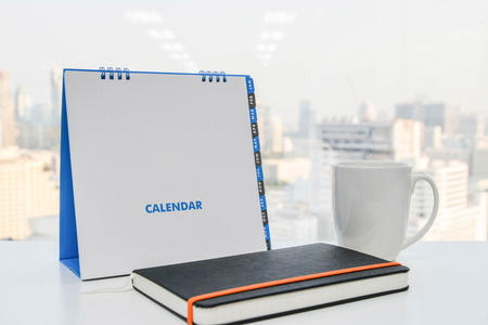 sunday paper: White Calendar and a cup of coffee and notebook on the white table Stock Photo