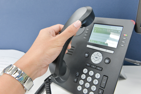 Human hand picking up the telephone