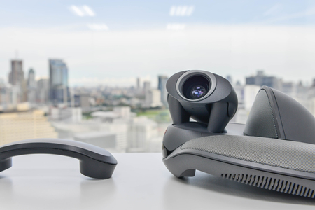 ip cam: Video Conference Device and Phone handset on the white table