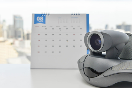 ip cam: Video Conference Device with calendar background on the white table