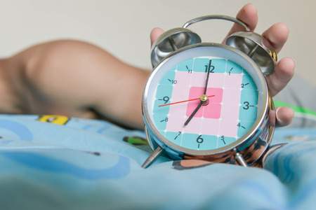 seven o'clock: sleepy man is expanding hand to stop the alarm clock that showing time for 7 AM