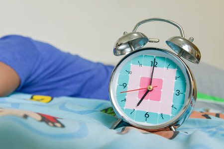 Man is still sleeping on the bed with Alarm clock is showing time for 7 AM