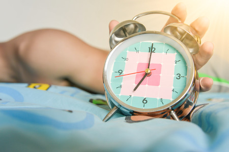 sleepy man is expanding hand to stop the alarm clock that showing time for 7 AM