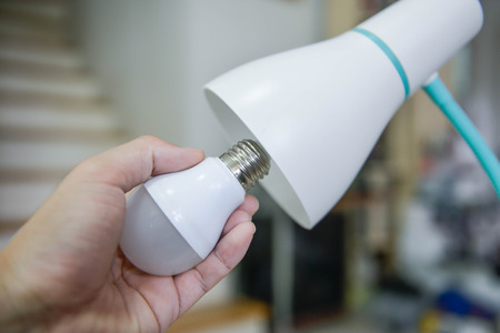 Man hand changing the LED bulb to white lamp - Saving energy concept Stock Photo