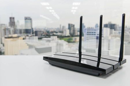 Black three poles wifi router on the white table Imagens
