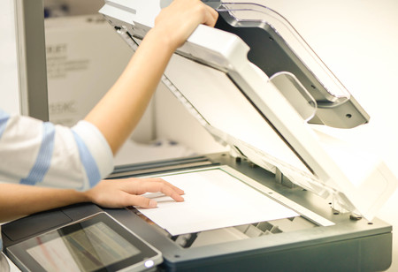 Business woman is using the printer to scanning the document