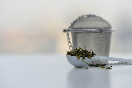 Dry tea leaves in a teaspoon with Tea strainer