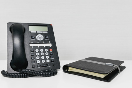 Black IP Phone and notebook on the white table