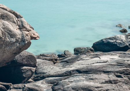 Rocks on the seashore with blue sea water Stock Photo