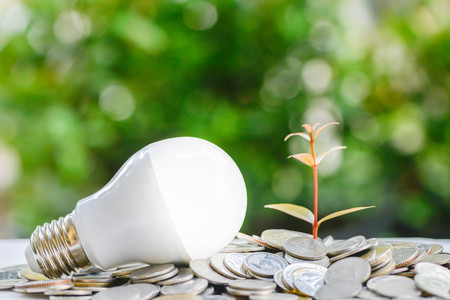 LED bulb on coin stacks with growing plant - Concept of saving energy Lizenzfreie Bilder
