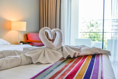 Handtuchgestaltung als Schwäne auf dem Bett im Hotel