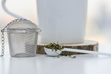 Dry tea leaves in a teaspoon with Tea strainer and cup Lizenzfreie Bilder