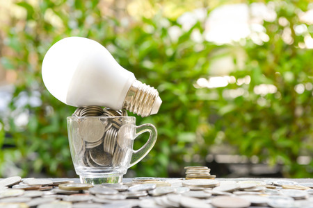 LED bulb with coins in the glass and sun light for concept of saving energy