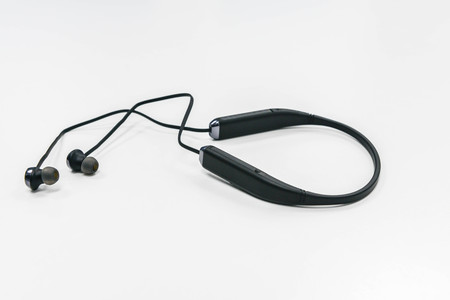 portable audio: Black wireless earphone on the white table Stock Photo