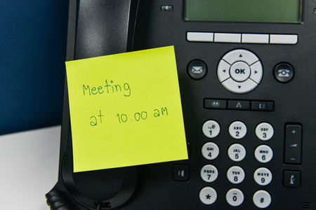 attached: Paper note with meeting time at 10.00 AM wording is sticked on the IP Phone Stock Photo