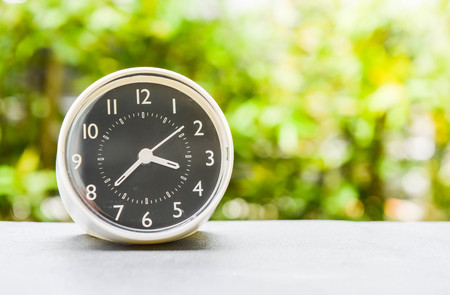 Clock is on the table with green nature background