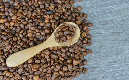 Coffee bean and wooden spoon on the wooden background