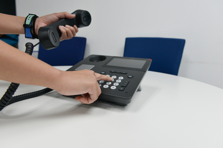 Business woman hand is holding the IP phone hand set and put to the number pad to dial the call