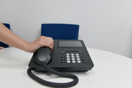 Business woman hand is holding the IP phone hand set to answer the call