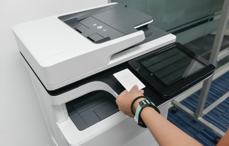 Business woman hand is using smart card with printer to printing document