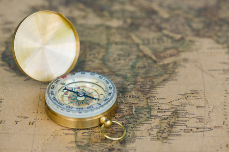 Close up ancient golden compass on the ancient map