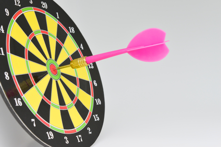 Close up pink darts arrow on the target center of dartboard with white background for business goal concept Stock Photo