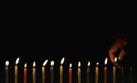 Human hand is lighting the birthday candle with lighter in the darkness