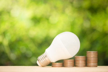LED bulb on the growing coin stack with green nature background on warm light tone for saving energy concept Standard-Bild - 104275503