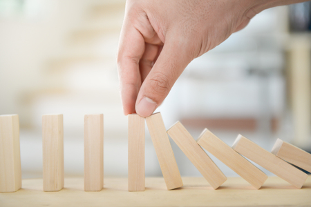 Man hand is holding the wooden block of tumbling tower to stop falling for business concept