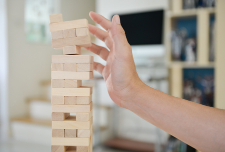 Man hand reach out to protect the tumbling blocks during a game Stock Photo